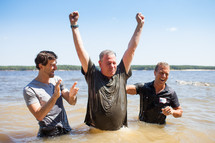 a man celebrating after his baptism in water outdoors