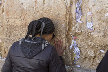 a woman praying against a wall
