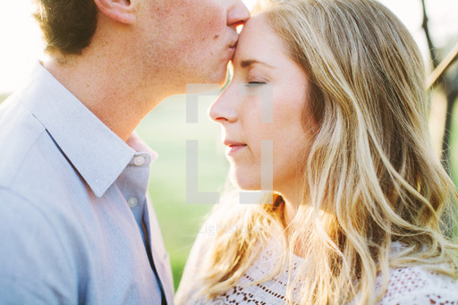A man kissing a woman on the forehead — Photo — Lightstock