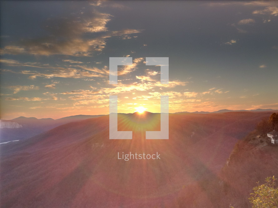sunburst at sunset moving behind a mountain