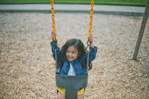 A little girl on a swing at the playground.
