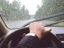 hand on a steering wheel driving in the rain