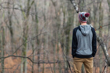 a teen boy standing in a forest in fall