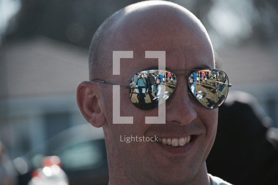 reflection of a crowd in a man's sunglasses