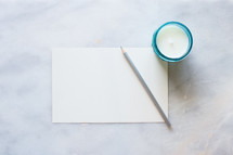 silver colored pencil, plain white paper, and candle on a table