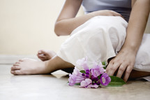 legs of a woman sitting on the floor with flowers