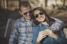 A young couple wearing sunglasses smiling together