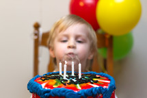 Child blowing out candles on a birthday cake.