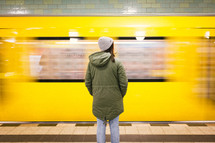 woman standing in front of a passing subway train