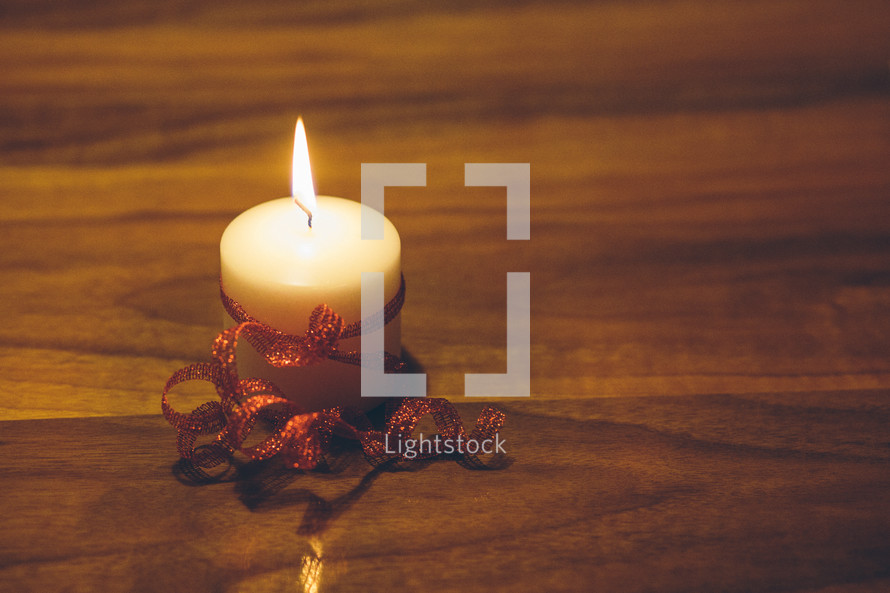 flame on a white candle wrapped in red ribbon