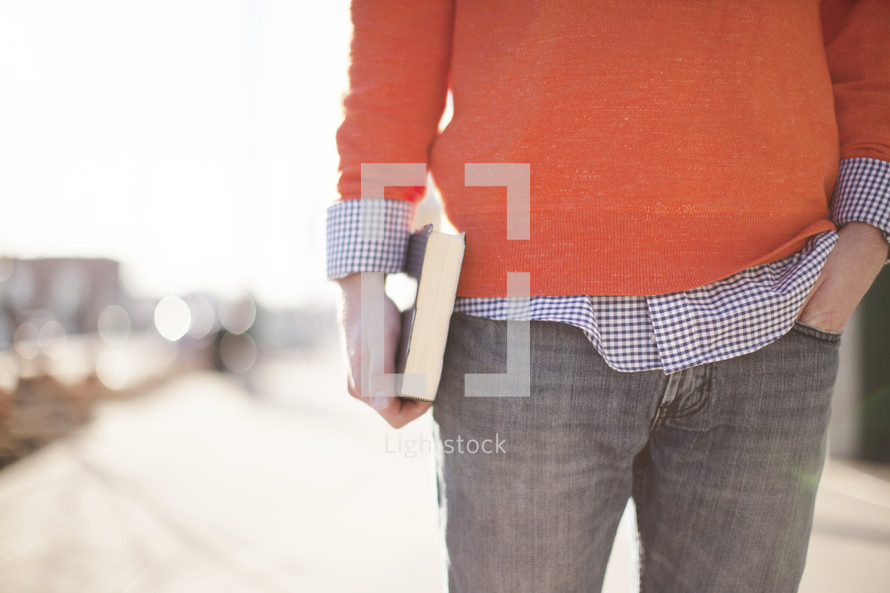 a college aged man holding a Bible at his side in the city