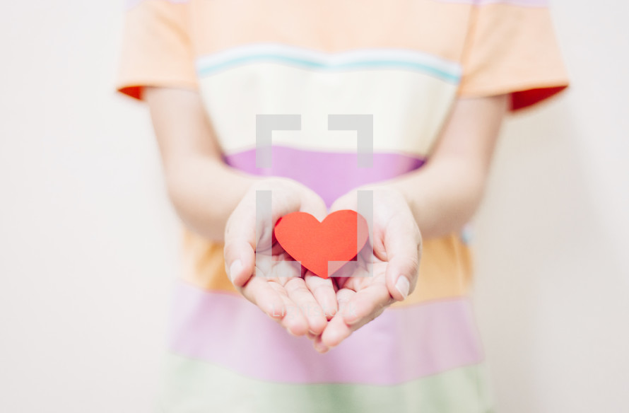 a boy holding a paper heart in cupped hands