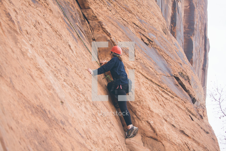a young person rock climbing on a steep cliff