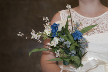 a bride holding a bouquet of blue flowers