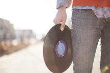 man holding a record at his side