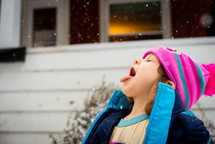 A little girl catching snow on her tongue while wearing winter clothes outside.