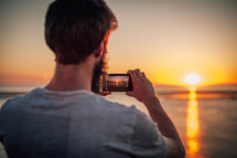 Guy capture sunset on the ocean