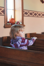a child sitting in church pews