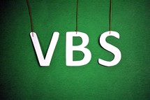 "The letters, ""VBS,"" hanging from strings on a green background."