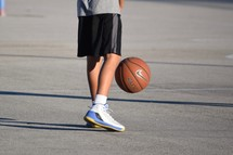 a boy on an outdoor basketball court playing ball