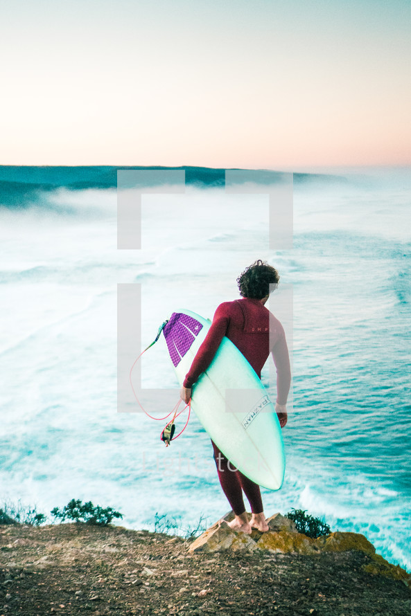 surfer standing on a beach with his surfboard