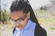 an African American teen girl in reading glasses looking down