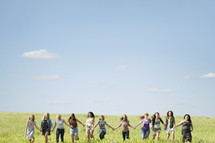 Teen girls holding hands, running through a field.