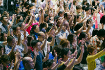 raised hands in worship at a conference