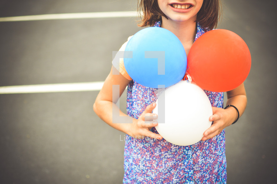 girl child holding patriotic colored balloons