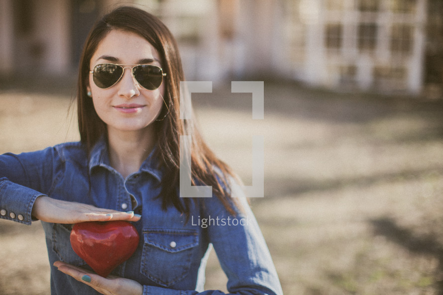 A young woman in sunglasses holding a red heart