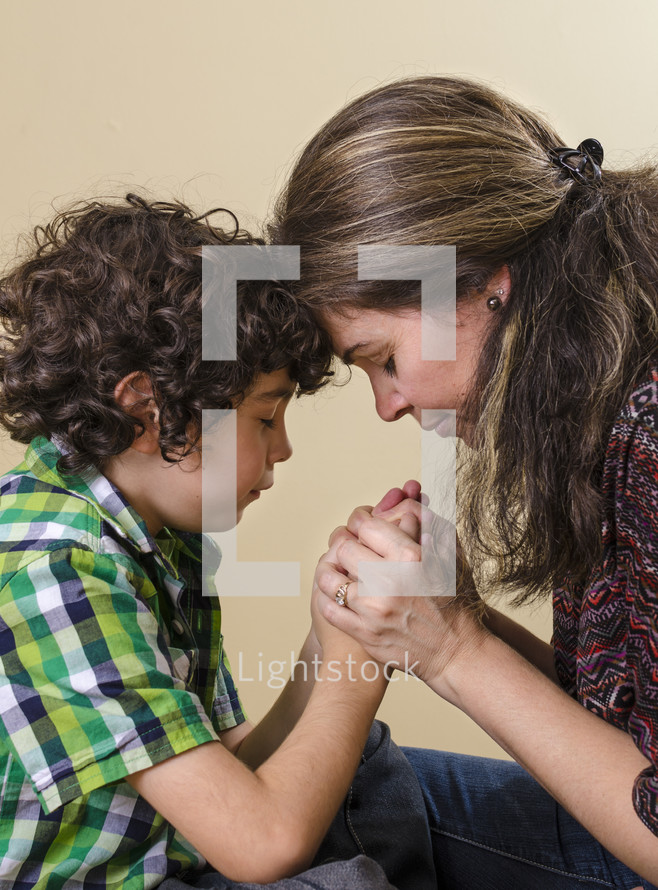 mother and son holding hands in prayer