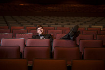 man in a tuxedo sitting in an empty auditorium