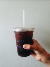 a hand holding a plastic cup full of soda
