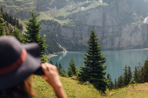 woman taking photo of beautiful waterfall and mountain lake
