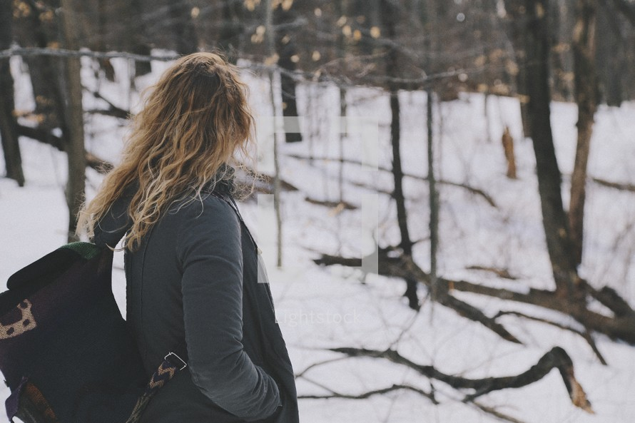 a woman with a backpack walking in a snowy forest