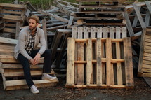 a man sitting next to a pile of old pallets