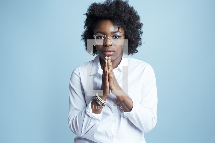 young African American female model posing with praying hands