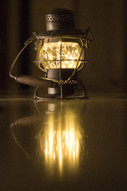 glowing lantern reflecting on wooden floor