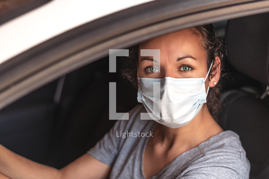 woman driving a car wearing a face mask