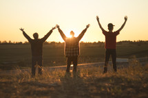 men standing in a field with raised hands