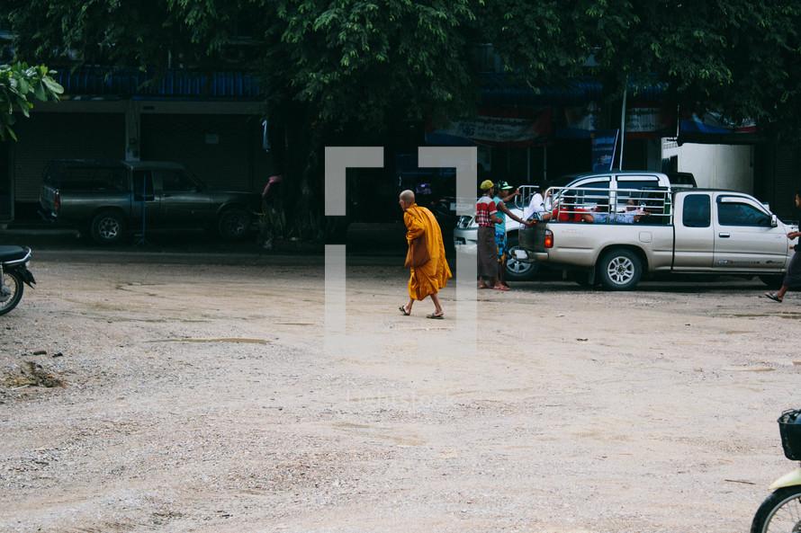a monk walking across a parking lot