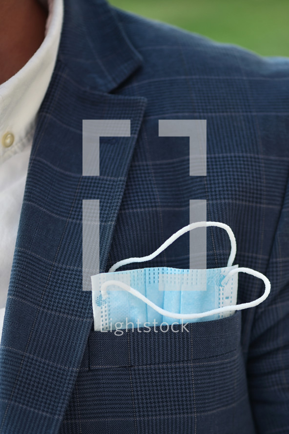 a businessman with a face mask in his pocket