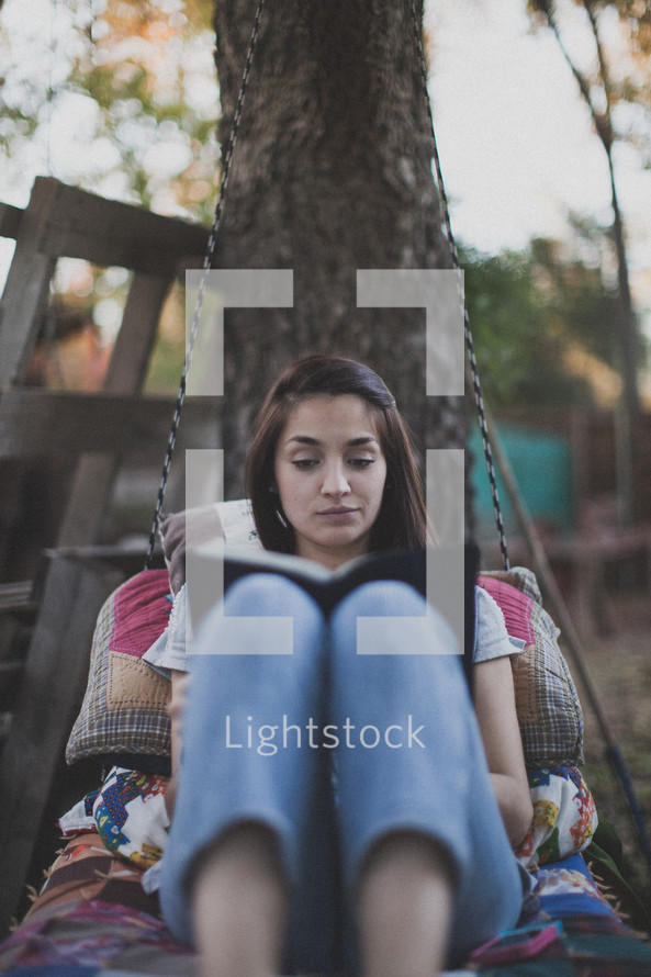 A young woman sitting on a swing and reading the Bible