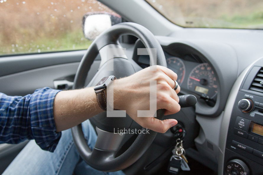 a man wearing a smartwatch driving a car