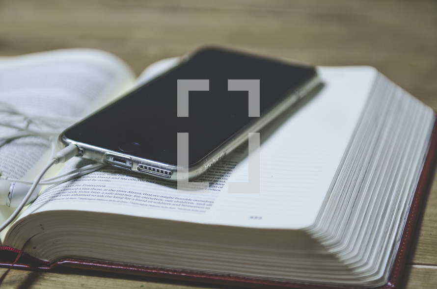 cellphone and earbuds on an open Bible
