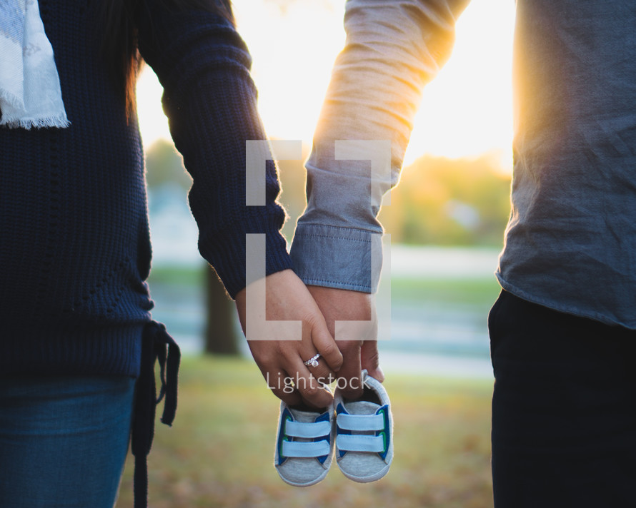 pregnancy announcement, parents holding baby shoes