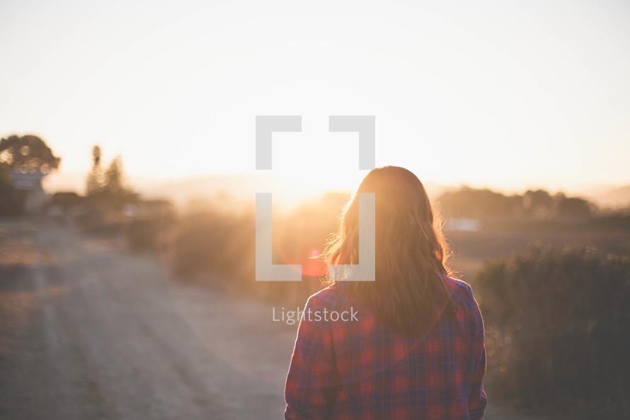 A woman walking outdoors under intense sunlight at sunset
