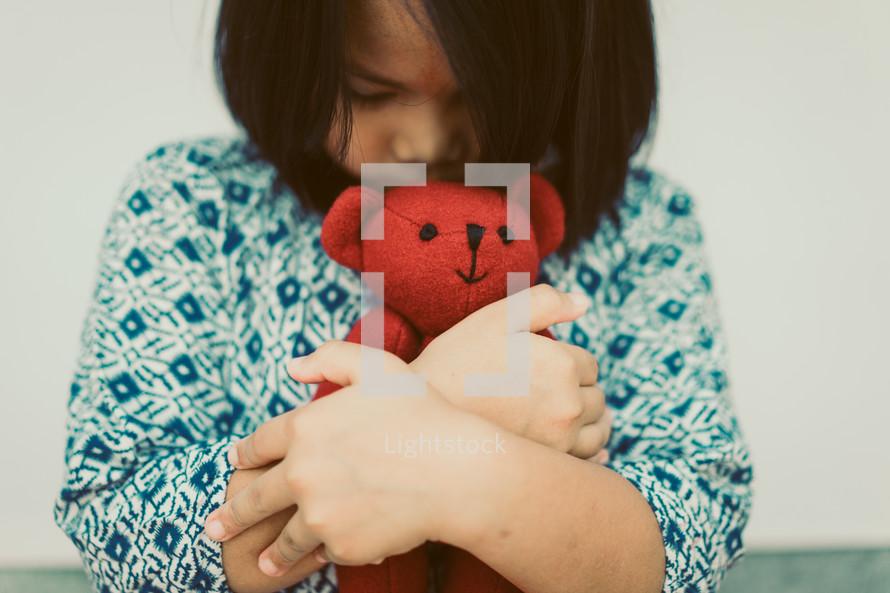 toddler hugging a teddy bear