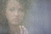 Young girl  looking out a frosted window.