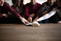A group sitting on a couch and pointing at a Bible verse